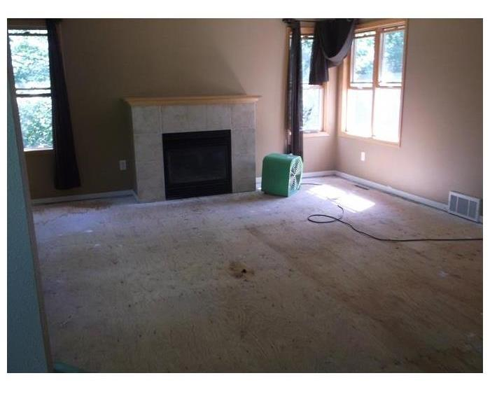 Image of sitting room with fireplace after carpet and pad removed.