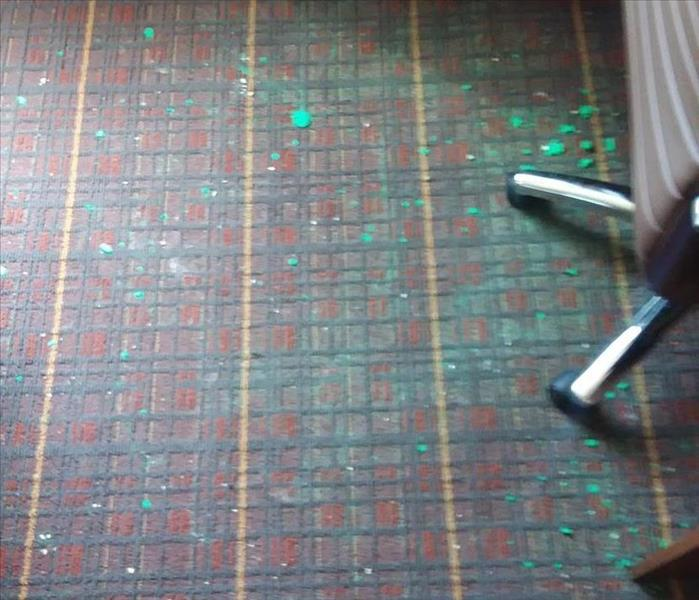 Picture of burgundy plaid carpet covered with green Play-Doh, before cleaning.