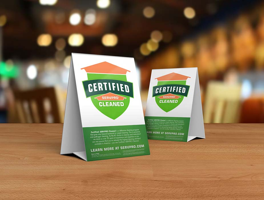 Table tent signs describing the Certified: SERVPRO Cleaned program on top of a wooden table.